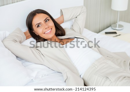 Relaxing in hotel room. Top view of beautiful young businesswoman in suit holding hands behind head and smiling while lying in bed at the hotel room - stock photo