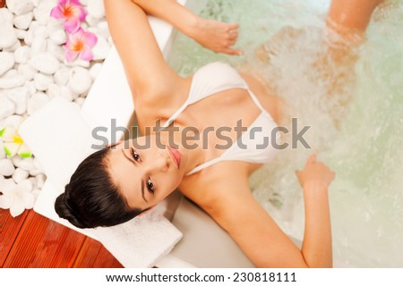 Relaxing in Jacuzzi. Top view of attractive young woman relaxing in hot tub and looking at camera - stock photo