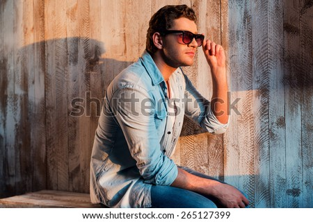 Relaxing in sun rays. Handsome young man looking away and adjusting his sunglasses while sitting against the wall - stock photo