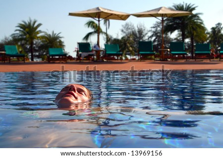 Relaxing In The Pool A young woman in a swimming pool. Ideal shot to express summer feeling and vacation. - stock photo