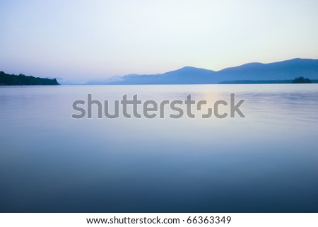 Relaxing lake scene, slight cooling tone added. Long exposure for soft water reflections. - stock photo