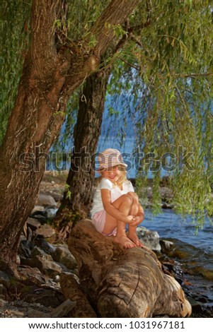 relaxing little girl sitting on a stone at the Lago Maggiore in Italy