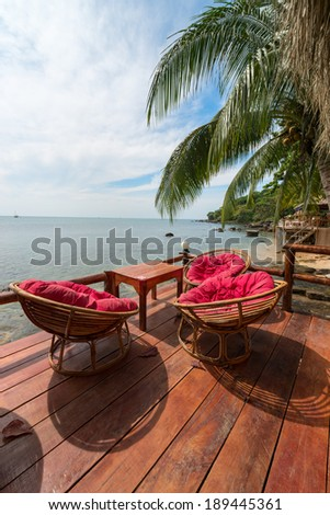 Relaxing lounge chair relax area in beach cafe by the blue sea  - stock photo