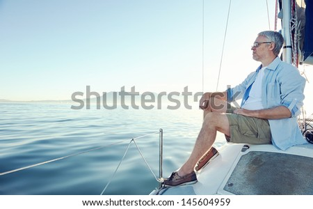 relaxing man sitting on boat sailing on ocean happy and carefree - stock photo