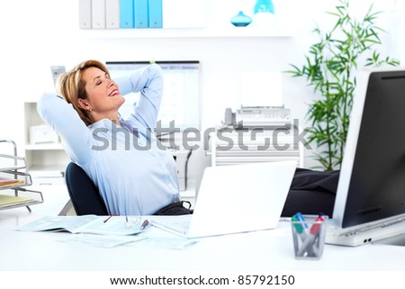 Relaxing mature business woman. In a modern office. - stock photo