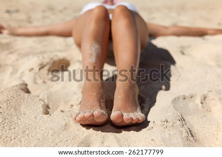 Relaxing on a beach. Feet with sand. - stock photo