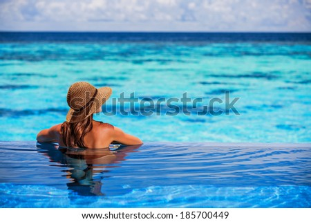 Relaxing on beach resort, back side of sexy woman enjoying seascape from endless pool, luxury summer vacation, travel and tourism concept - stock photo
