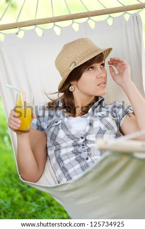 Relaxing on hammock with coctail - stock photo