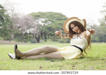 Relaxing on the lawn. Woman wearing hat sitting and relaxing on the grass in the park.