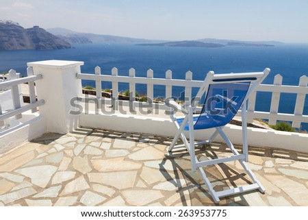 relaxing one blue chair with view of caldera, Santorini, Greece