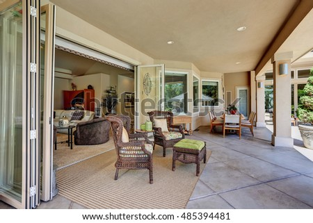 Relaxing outdoor seating arrangement of luxury house. Wicker chairs with ottoman. Northwest, USA