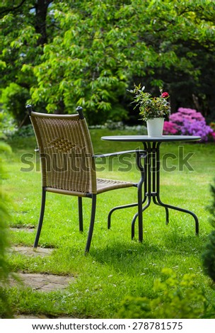 Relaxing place-table and chair in flowering garden. - stock photo