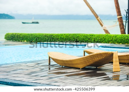 Relaxing rattan bed beside swimming pool,vacation and holidays - stock photo