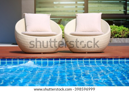 Relaxing rattan chairs with pillows beside swimming pool - stock photo