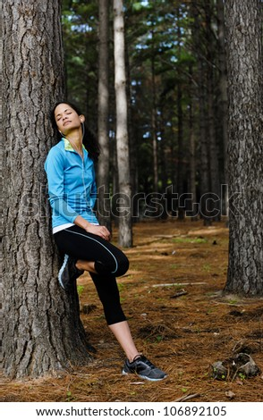 Relaxing runner resting and listening to music on headphones in forest after training. serene scene with copyspace