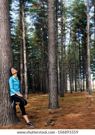 Relaxing runner resting and listening to music on headphones in forest after training. serene scene with copyspace - stock photo