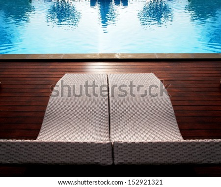 Relaxing seats near the swimming pool and blue sky - stock photo