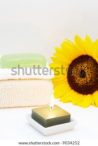 Relaxing spa scene with body sponge, face towel, glycerin soap, candle and sunflower in the background - stock photo