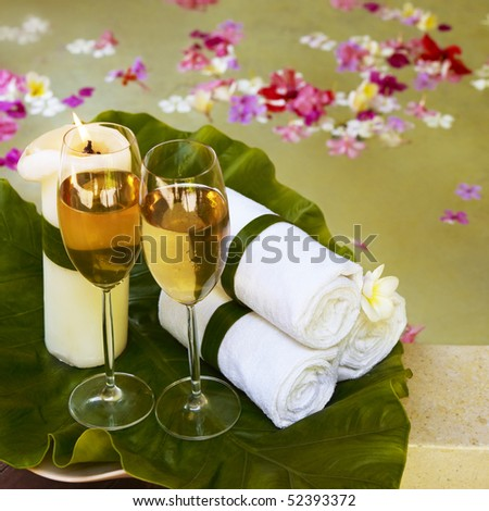 Relaxing spa still life with towels. Flowers in water on background. - stock photo