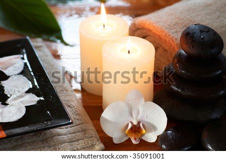 relaxing spa with candles orchids towels and stones on wet wooden background - stock photo