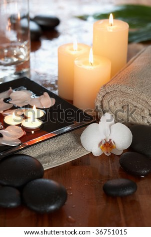 relaxing spa with candles orchids towels and stones on wooden background - stock photo