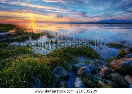 Relaxing summer river sunset with green grass blue skies and distant mountains - stock photo