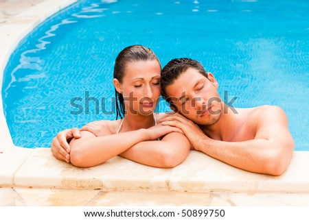Relaxing summer wet couple in blue swimming pool - stock photo
