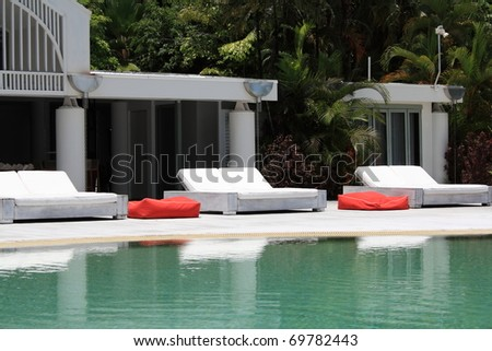 relaxing sunbeds at a pool - stock photo