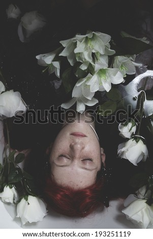 Relaxing, Teen submerged in water with white roses, romance scene - stock photo