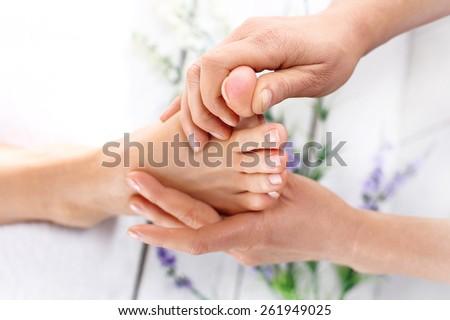 Relaxing Thai foot massage. Masseuse massaging woman's foot. - stock photo