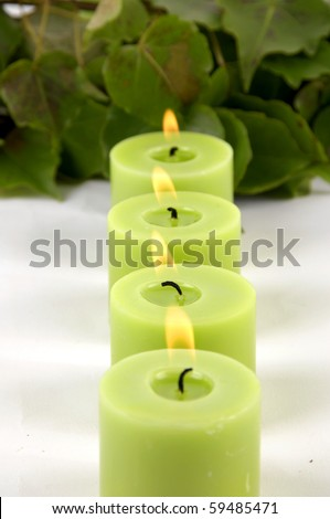 relaxing treatment â??row of green candle with leaf - stock photo