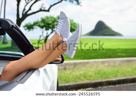 Relaxing vacation car road trip travel with feet up the window. Convertible car holiday concept with female legs in front of Oahu landmark : Chinaman's Hat in Hawaii, USA. - stock photo