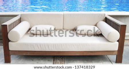Relaxing white sofa with pillows beside swimming pool - stock photo