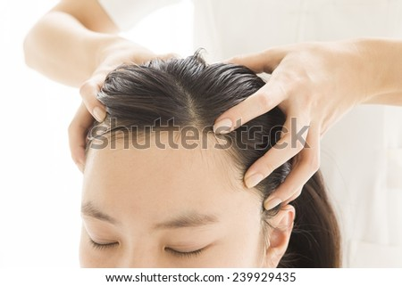 Relaxing woman having a head massage - stock photo