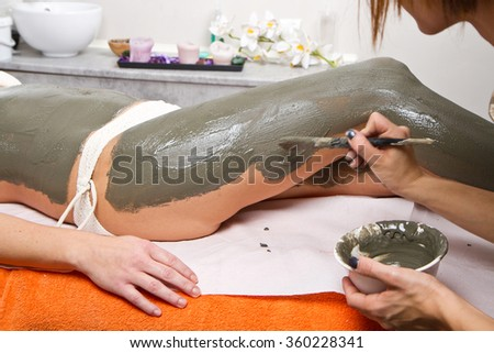 relaxing woman lying on a massage table receiving a mud treatment  - stock photo