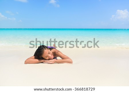 Relaxing woman on beach vacation sleeping on sand. Beautiful girl lying down under the sun tanning in perfect paradise white sand beach and pristine blue ocean background. - stock photo