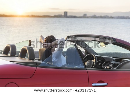 Relaxing woman on the beach in the cabriolet car without a roof. Vacation, holiday, journey to the sea or the resort. - stock photo