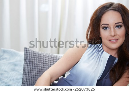 Relaxing woman sitting comfortable in sofa lounge chair smiling happy looking at camera. Resting beautiful young multicultural asian caucasian girl in her 20s . - stock photo