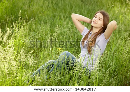 Relaxing woman sitting in grass enjoying fresh air with hands clasped over her head - stock photo