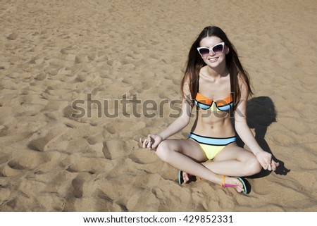 Relaxing young woman on the beach in a Lotus pose. Smiling attractive girl sit on the sand beach. - stock photo