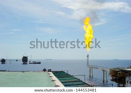Releasing gas from oil and gas offshore platform - stock photo