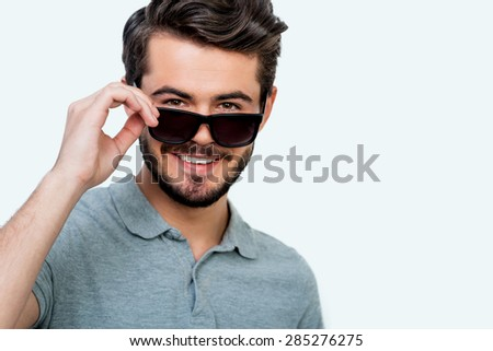 Reliable smile. Cheerful young man adjusting eyewear and smiling at camera while standing against white background - stock photo