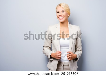 Reliable smile. Confident young businesswoman holding hands on her jacket and looking at camera while standing against grey background - stock photo