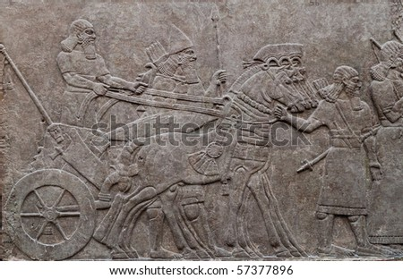 Relief of ancient assyrian warriors in a horse drawn chariot - stock photo