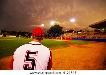 Relief pitcher watching his team play baseball at night - stock photo