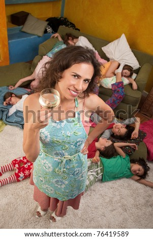 Relieved Hispanic woman drinking wine after kids fall sleep - stock photo