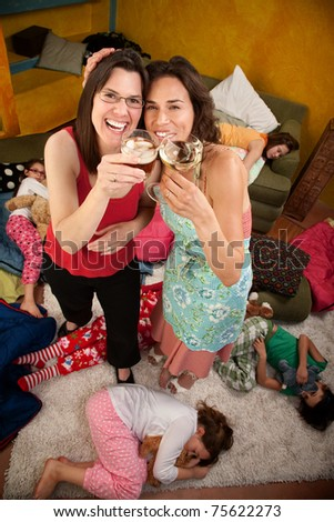 Relieved mom and babysitter drinking alcohol after kids go to sleep - stock photo