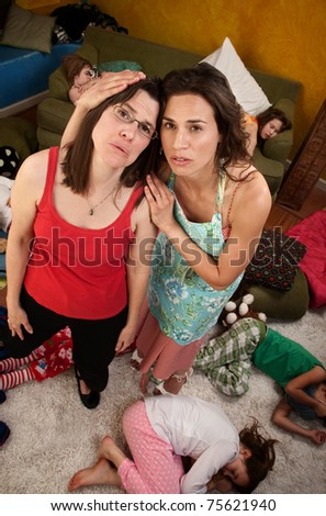 Relieved mothers embrace after children fall asleep - stock photo