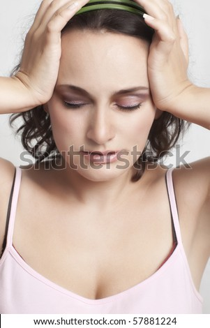 relieved young woman with closed eyes holding her head