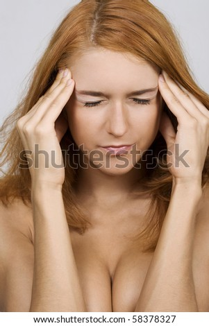 Relieved young woman with closed eyes holding her head - stock photo